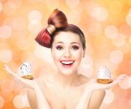 Mooie vrouw met een boogkapsel die een cake houden Stock Foto