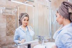 Mooie vrouw met een handdoek op haar hoofd, die in de spiegel kijken royalty-vrije stock foto's