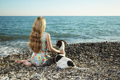 Mooie vrouw met een hond op het strand Stock Fotografie