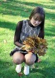 Mooie vrouw met esdoornbladeren stock fotografie