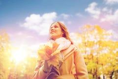 Mooie vrouw met esdoornbladeren in de herfstpark Stock Afbeelding