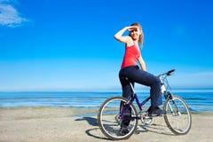 Mooie vrouw met fiets bij het overzees royalty-vrije stock afbeelding