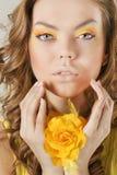 Mooie vrouw met gele bloem Stock Afbeeldingen