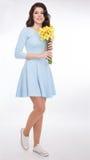 Mooie vrouw met gele narcissen Stock Fotografie