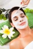 Mooie vrouw met gezichtsmasker bij kuuroord Royalty-vrije Stock Foto's