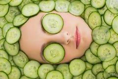 Mooie vrouw met gezichtsmasker van komkommerplakken op gezicht Stock Fotografie