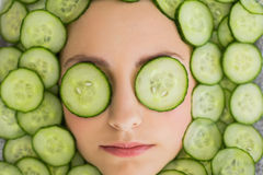 Mooie vrouw met gezichtsmasker van komkommerplakken op gezicht Stock Foto