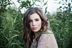 Mooie vrouw met gezonde huid en bruin krullend haar op groene grasachtergrond stock afbeeldingen