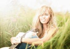 Mooie vrouw met gitaarzitting op gras. Stock Afbeeldingen