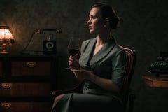 Mooie vrouw met glas wijn in retro binnenland royalty-vrije stock foto