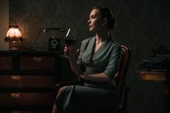 Mooie vrouw met glas wijn in retro binnenland stock fotografie