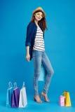 Mooie vrouw met glazen en een hoed op een blauwe achtergrond in de volledige groei, het winkelen, shopaholic pakketten, Stock Foto's