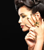 Mooie vrouw met gouden spijkers en stijlmake-up royalty-vrije stock afbeelding