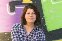 Mooie vrouw met groene ogen tegen een graffitiachtergrond Stock Foto