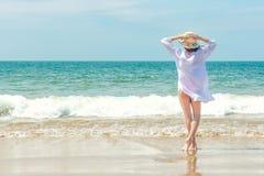 Mooie vrouw met handen die omhoog op het zandstrand ontspannen met overzeese mening, genietend van de de zomerwind en het geluid  stock foto's