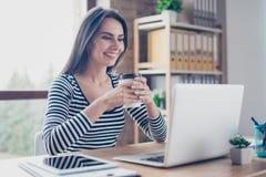 Mooie vrouw met het richten van glimlach het drinken koffie en het lezen van nieuws stock fotografie
