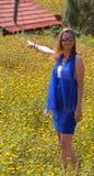 Mooie vrouw met huis op een bloemgebied stock fotografie