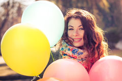 Mooie vrouw met kleurrijke ballons in het de lentepark Stock Foto