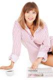 Mooie vrouw met kop van koffie en een krant Stock Fotografie