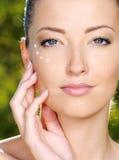 Mooie vrouw met kosmetische room dichtbij ogen Royalty-vrije Stock Afbeeldingen