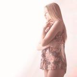 Mooie vrouw met lang blond haar in roze licht royalty-vrije stock foto