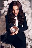 Mooie vrouw met lang donker haar die elegant kostuum dragen, die een grote decoratieve diamant houden Royalty-vrije Stock Fotografie