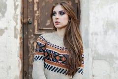 Mooie Vrouw met lang haar in de wintertrui Gezond haar Grijze achtergrond stock foto