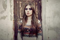 Mooie Vrouw met lang haar in de wintertrui Gezond haar Grijze achtergrond stock fotografie