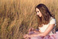 Mooie vrouw met lang haar die witte zijdebovenkant dragen en roze die rokzitting op het gele gebied en wat betreft droog gras ver Stock Foto's