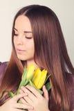 Vrouw met lang haar met gele tulpen Stock Fotografie