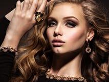 Mooie vrouw met lang krullend haar en gouden juwelen royalty-vrije stock fotografie