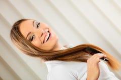 Mooie vrouw met lange haar en borstel Stock Afbeelding