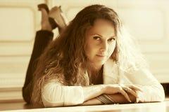 Mooie vrouw met lange krullende haren die op de vloer liggen Stock Afbeelding