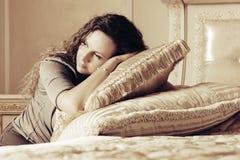 Mooie vrouw met lange krullende haren in een slaapkamer Stock Afbeeldingen