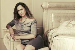 Mooie vrouw met lange krullende haren in een slaapkamer Stock Foto's
