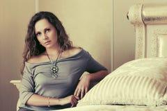 Mooie vrouw met lange krullende haren in een slaapkamer Stock Fotografie