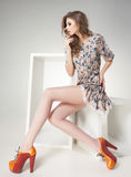 Mooie vrouw met lange sexy benen in de zomerkleding het stellen Stock Afbeelding