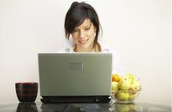 Mooie vrouw met laptop over wit Stock Afbeelding