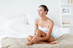 Mooie vrouw met naakte benen op bed thuis stock afbeelding