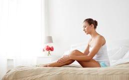 Mooie vrouw met naakte benen op bed thuis stock foto