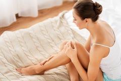 Mooie vrouw met naakte benen op bed thuis royalty-vrije stock afbeelding