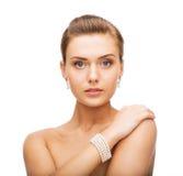 Mooie vrouw met pareloorringen en armband stock afbeelding
