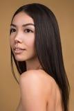 Mooie Vrouw met Perfect die de Studioportret van de Huidschoonheid op Beige Achtergrond wordt geïsoleerd Stock Foto's