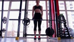 Mooie vrouw met perfect geschikt lichaam die Roemeense deadliftoefening in gymnastiek doen stock videobeelden