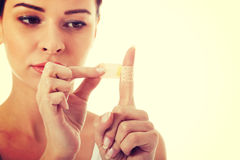 Mooie vrouw met pleister op haar vinger Stock Foto's