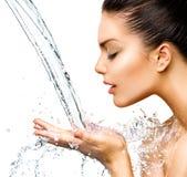 Mooie vrouw met plonsen van water Stock Afbeeldingen
