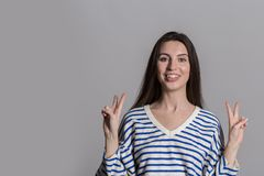 Mooie vrouw met pluizig haar, terloops gekleed tegen een grijze studiomuur stock foto