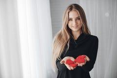 Mooie vrouw met rode harten in liefdedag Stock Fotografie