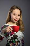 Mooie vrouw met rode kop thee of koffie Royalty-vrije Stock Foto's