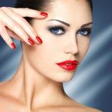 Mooie vrouw met rode spijkers en blauwe ogen Stock Fotografie